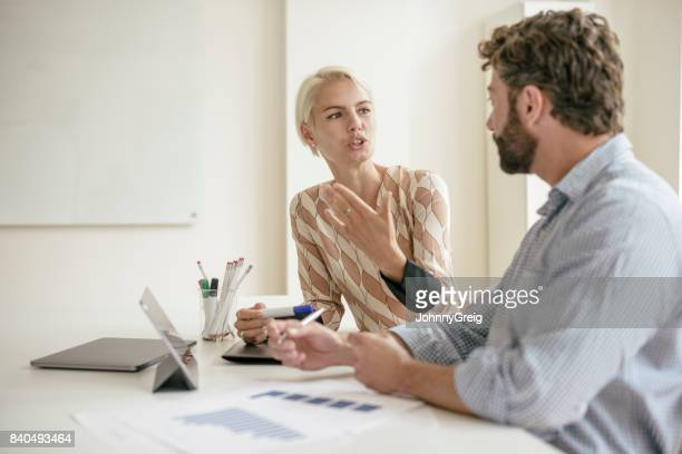 Mid adult businesswoman explaining and gesturing to coworker in office