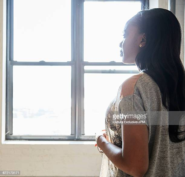 Mid adult businesswoman gazing through new office window
