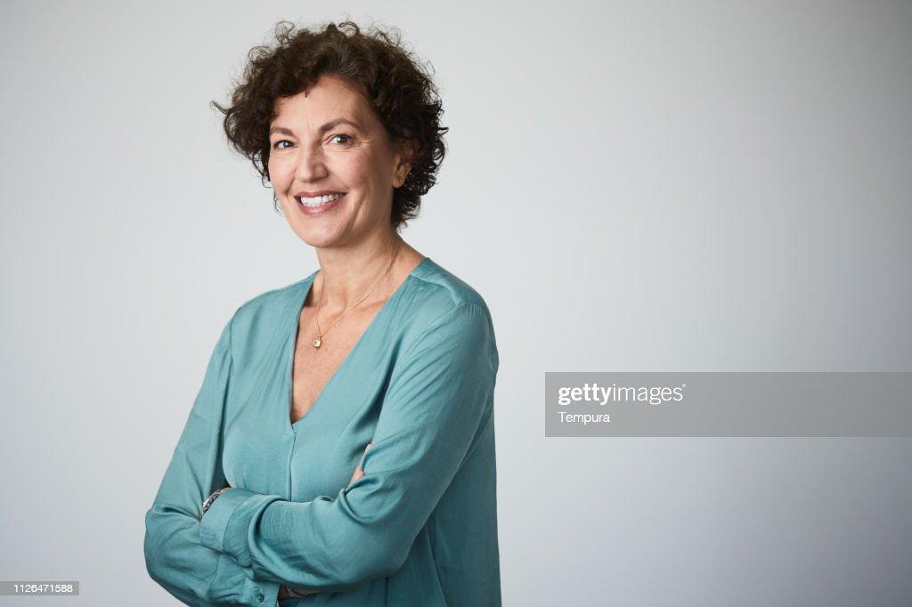 Mid adult businesswoman headshot on grey background. : Stock Photo