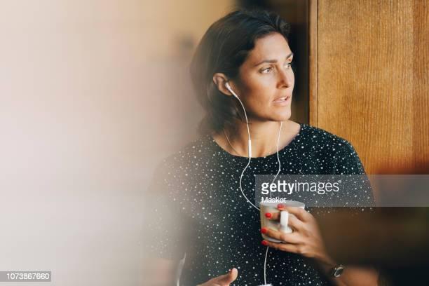 mid adult businesswoman holding coffee cup while talking on earphones in office - werkneemster stockfoto's en -beelden
