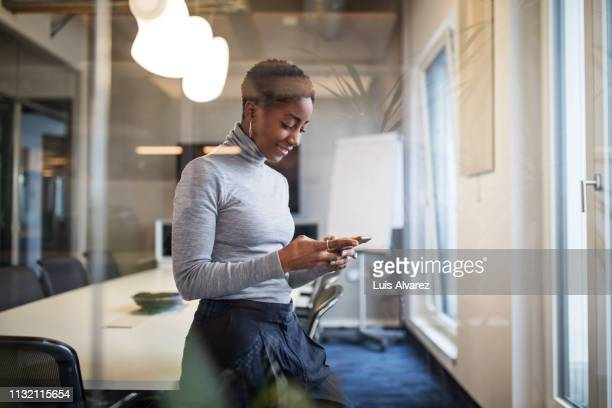 mid adult businesswoman in conference room using cell phone - mock turtleneck stock pictures, royalty-free photos & images