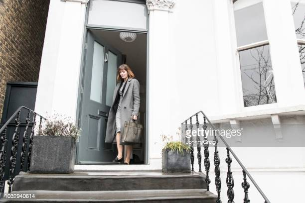 mid adult businesswoman leaving house and closing front door - closing stock photos and pictures