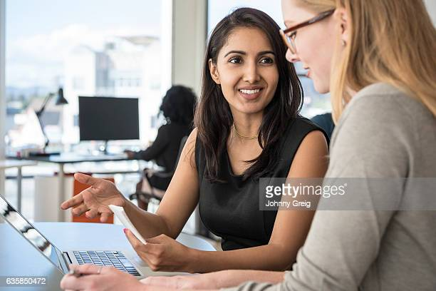 Mid adult businesswoman listening to female colleague in office