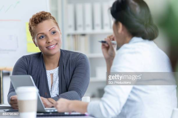 Mid adult businesswoman listens to coworker's new ideas