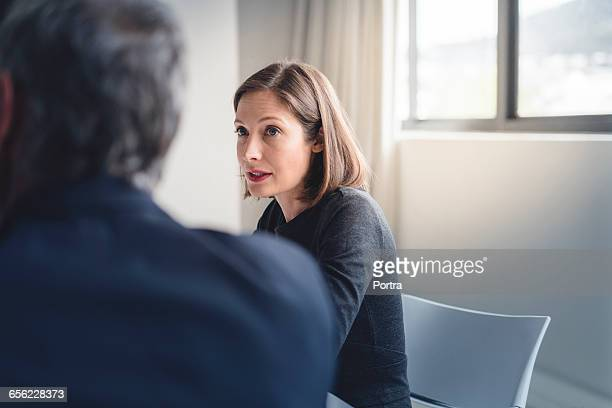 Mid adult businesswoman looking at colleague