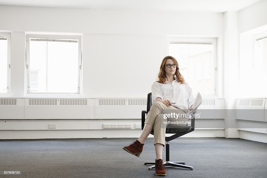 Mid adult businesswoman on office chair in new office : Stock Photo