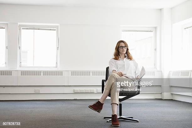 mid adult businesswoman on office chair in new office - white pants stock pictures, royalty-free photos & images