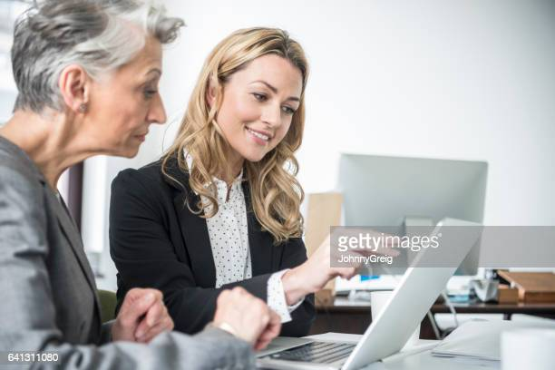 Mid adult businesswoman pointing to her laptop with female colleague