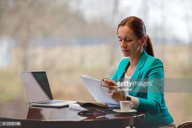 Mid adult businesswoman reading reports in the office.