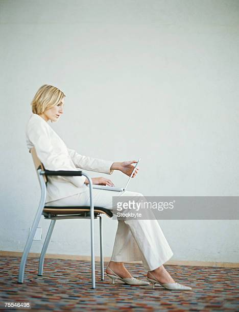 Mid adult businesswoman sitting in chair using laptop,side view