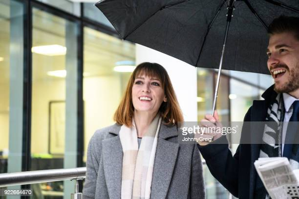mid adult businesswoman smiling under umbrella with man - social grace stock pictures, royalty-free photos & images