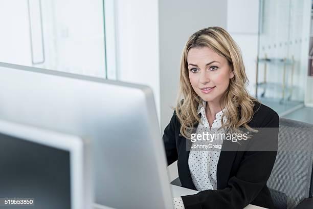 Mid adult businesswoman using desktop computer, high angle
