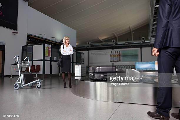 Milieu âge Femme d'affaires en attente pour les bagages dans la zone de retrait des bagages de l'aéroport à nouveau