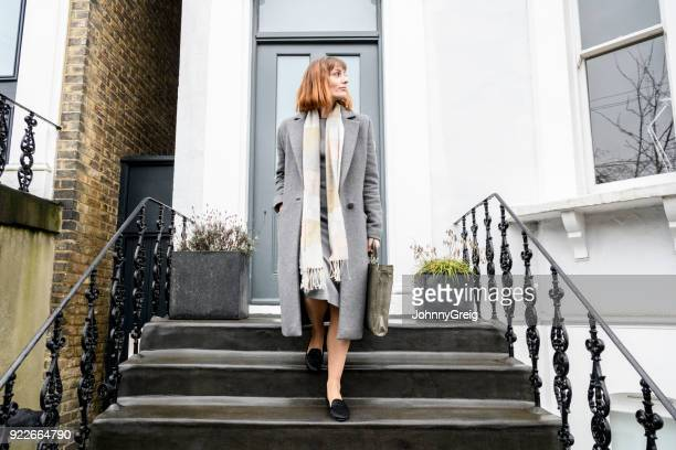 mid adult businesswoman walking down steps outside house on way to work - leaving stock pictures, royalty-free photos & images