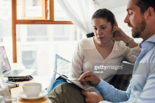 Mid adult businesswoman with male colleague using digital tablet in office