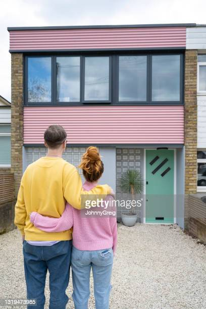 mid adult caucasian couple admiring their new home - mid adult couple stock pictures, royalty-free photos & images