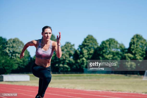 mid adult caucasian female athlete sprinting on sports track - sprint stock pictures, royalty-free photos & images