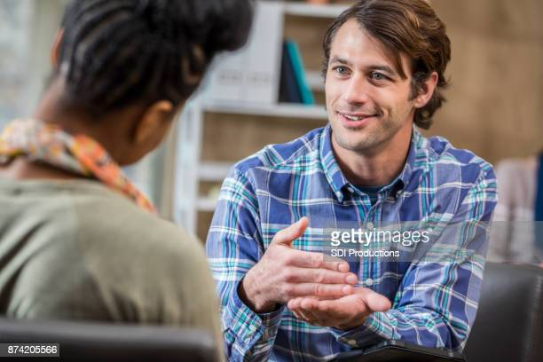 mid adult caucasian man discusses something with therapist - counseling stock pictures, royalty-free photos & images