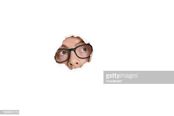 mid adult caucasian man looking away from ripped paper hole - peeping holes ストックフォトと画像