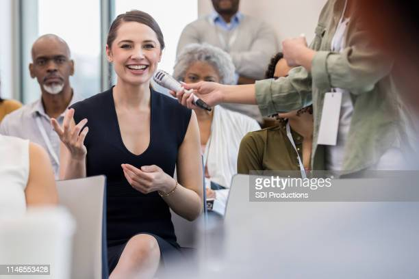 mid adult caucasian woman asks question - panel discussion stock pictures, royalty-free photos & images