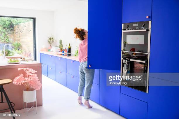 mid adult caucasian woman reaching into refrigerator - pink colour stock pictures, royalty-free photos & images