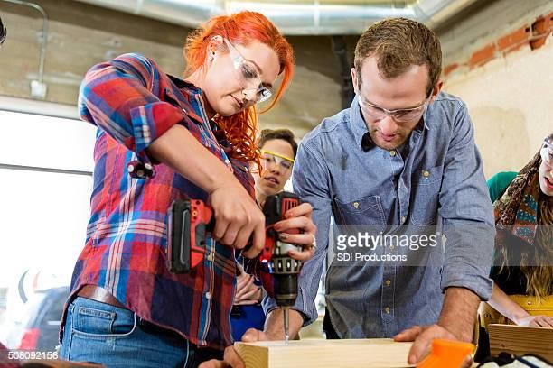 Kaukasischen Frau mittleren Alters mit macht Bohrmaschine in makerspace