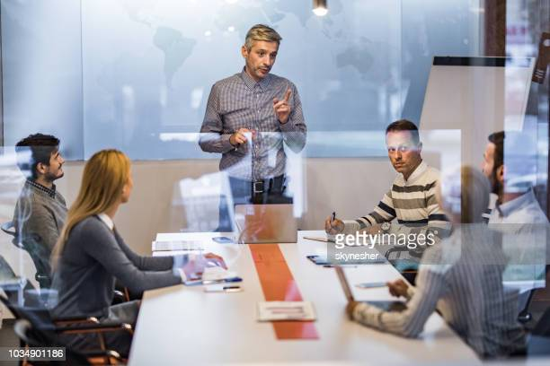 mid adult ceo talking to his team on a meeting in the office. - rules stock pictures, royalty-free photos & images