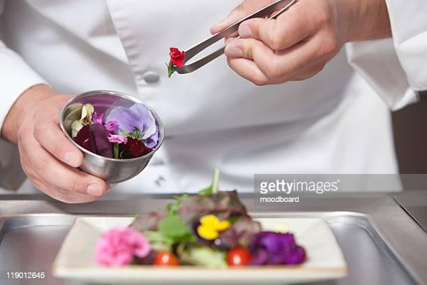 mid- adult chef arranges edible flowers on salad - comida flores fotografías e imágenes de stock
