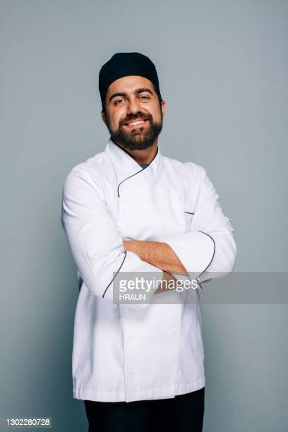 mid adult chef in uniform on a greyish background - chef stock pictures, royalty-free photos & images