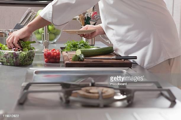 Mid- adult chef prepares salad