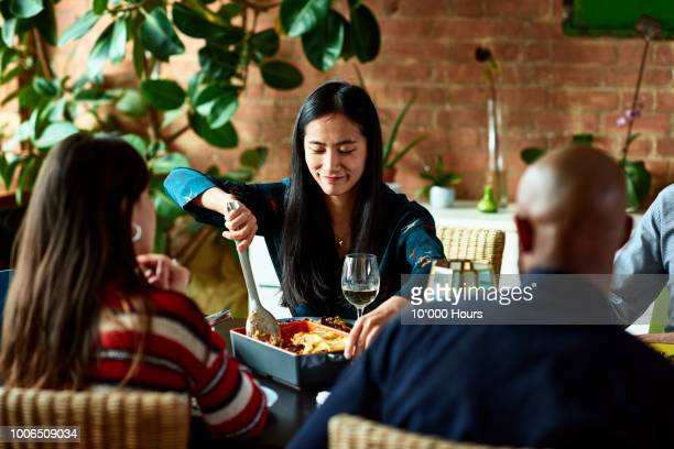 mid adult chinese woman serving home made dish at meal time - lasagna stock pictures, royalty-free photos & images