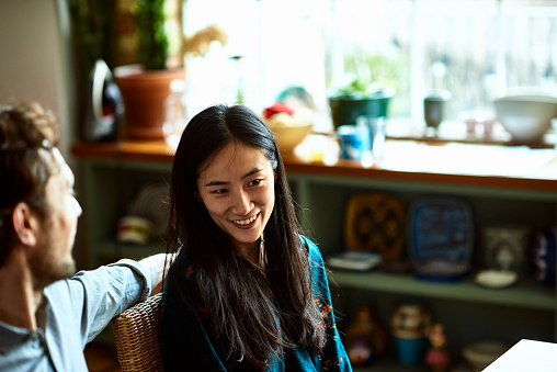 Mid adult Chinese woman with long hair sitting with man in kitchen - gettyimageskorea