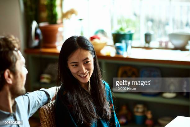 mid adult chinese woman with long hair sitting with man in kitchen - heterosexual couple stock pictures, royalty-free photos & images