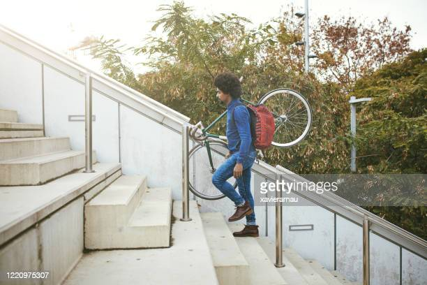 mid adult commuter with backpack carrying bicycle up stairs - staircase stock pictures, royalty-free photos & images