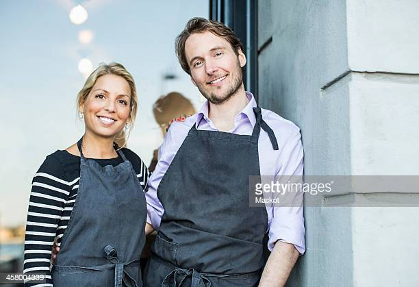 Mid adult confident owners standing at the entrance of restaurant
