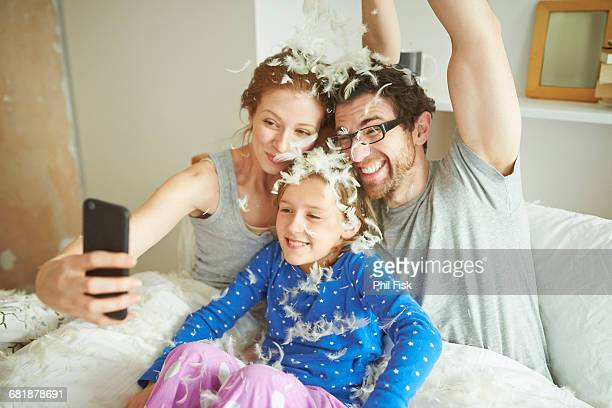 Mid adult couple and daughter covered in pillow fight feathers taking smartphone selfie in bed