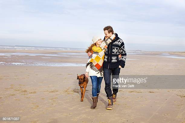 Mid adult couple and dog strolling on beach, Bloemendaal aan Zee, Netherlands
