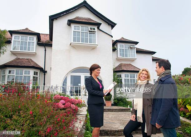Mid adult couple and estate agent outside house