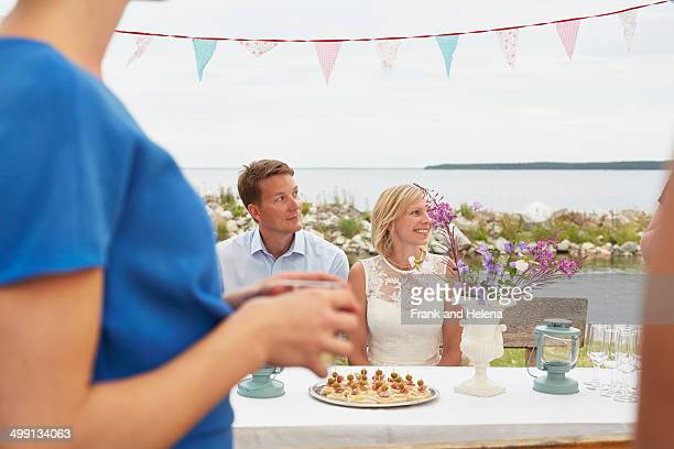 Mid adult couple and friends at wedding reception