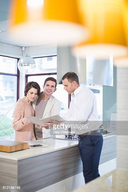 Mid adult couple and salesman looking at brochure in kitchen showroom