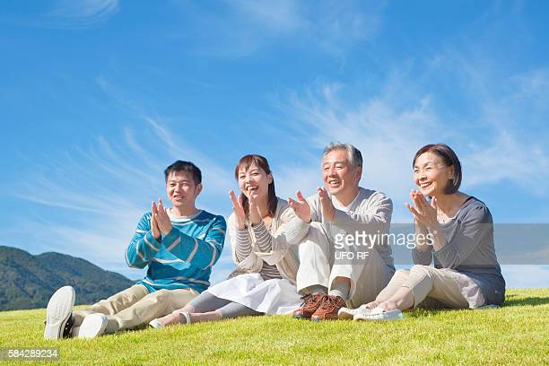 Mid Adult Couple and Senior Couple Clapping on Grass