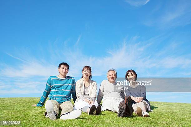 Mid Adult Couple and Senior Couple Sitting on Grass