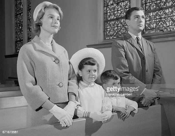 mid adult couple and their children praying in church - {{ collectponotification.cta }} foto e immagini stock