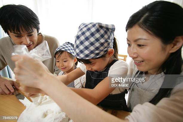 Mid adult couple and their two daughters sitting at the table and decorating a cake