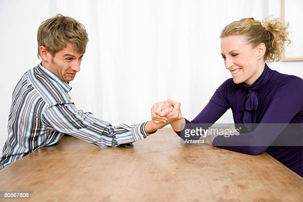 A mid adult couple arm wrestling