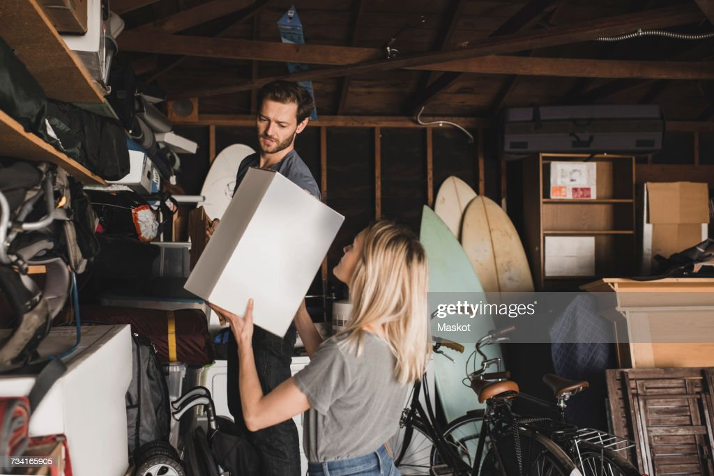 Mid adult couple arranging box in storage room : Stock Photo