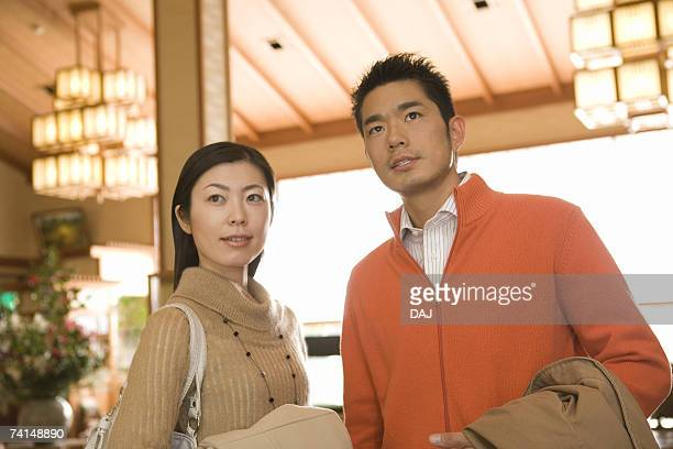 Mid Adult Couple Arriving at a Japanese Traditional Inn, Waist Up, Low Angle View, Differential Focus