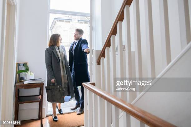 mid adult couple arriving home after work and entering hallway - arrival photos stock photos and pictures