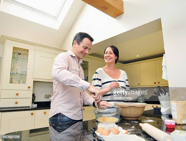 Mid adult couple baking in kitchen