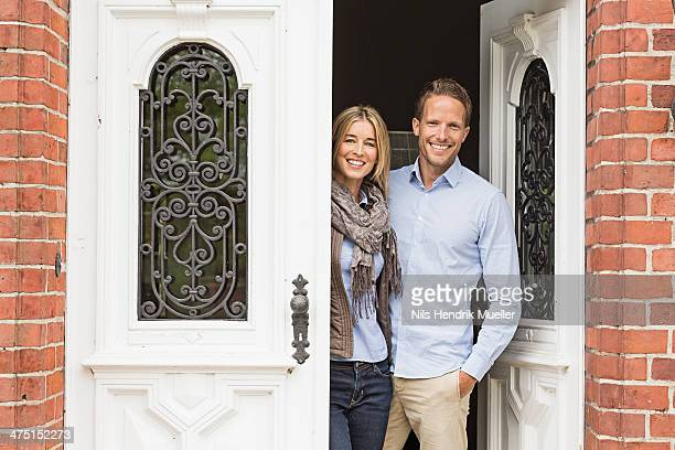 Mid adult couple by front door